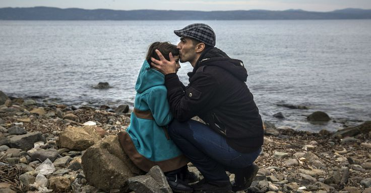 A Syrian man kisses his daughter shortly after disembarking from a dinghy at a beach on the Greek Island of Lesbos, on November, 2015.