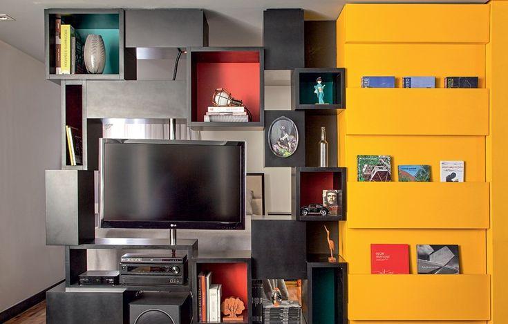 Os arquitetos Fernando Henrique de Abreu e Fabiana Rosello projetaram a estante com faces voltadas para a sala de estar e para o dormitório. No centro, a TV presa a uma haste de ferro articulada atende aos dois ambientes. Execução da marcenaria Arte Viva
