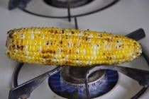 Roasting Corn. Preparation:  1.Shuck the corn. 2.Place an ear of corn on a burner. Feel free to utilize more burners and roast both ears of corn simultaneously. 3.Light your gas stove and turn heat to medium-high. 4.Roast corn, turning intermittently until it is charred in various places all around the corn. 5.Serve warm as it is, or with a dab of butter, a sprinkle of grated cheese, salt and pepper or a squirt of lemon juice.