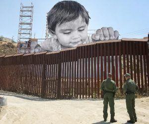 Dit kindje kijkt over de muur tussen de VS en Mexico