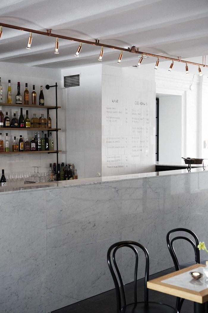 marble bar set against rough open shelving