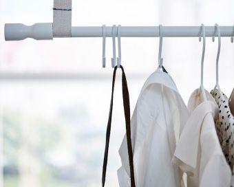 Hier hängt Kleidung an einer RÄCKA Gardinenstange in Weiß.