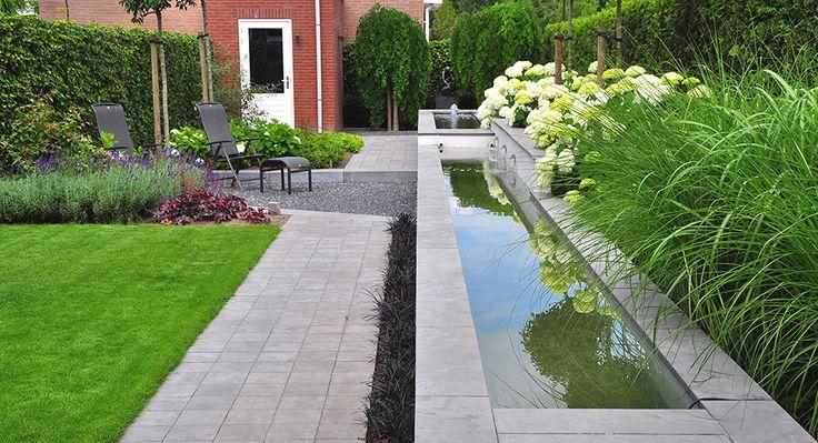 Strakke tuin met verhoogde vijverpartij in twee niveaus en verdiept gelegen zonneterras.