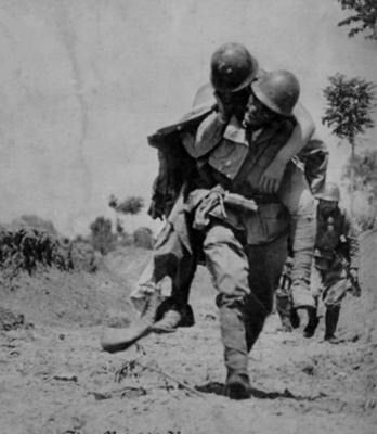 A Japanese Army soldier carries a wounded comrade off of the battlefield, China, 1939.