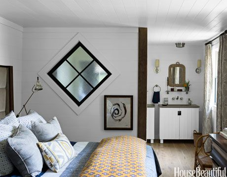 "Having admired diamond-shaped windows in stately old Syracuse houses, designer Thom Filicia introduced several in this lake house bedroom in Skaneateles as a repeating motif: ""I like how they float in a wall."" This one punctuates a screen wall between master bedroom and shower. On the bed, an orange duvet from Serena & Lily warms up a blue one from John Robshaw. The adjoining bathroom has twin Kohler vanities and Arhaus mirrors.   - HarpersBAZAAR.com"
