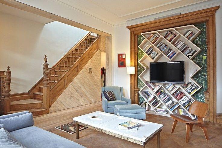 meuble TV bibliothèque avec des étagères murales inclinées, chaise design en bois, canapé en velours bleu ciel et fauteuil assorti