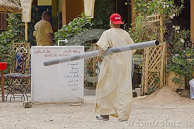 Architecture of the city Taroudant in Morocco, Africa . A man in traditional Moroccan dress goes to work, the pipe mount.