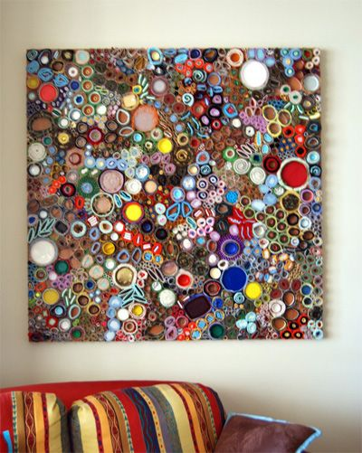 a variety of recycled - upcycled - materials such as fabric, paper, felt, foil, caps, carpet, metal, plastic, styrafoam, dried paint, beads, padding and cardboard, that have been hand-rolled into circles and swirls. Beautiful way to turn ordinary everyday objects into art.