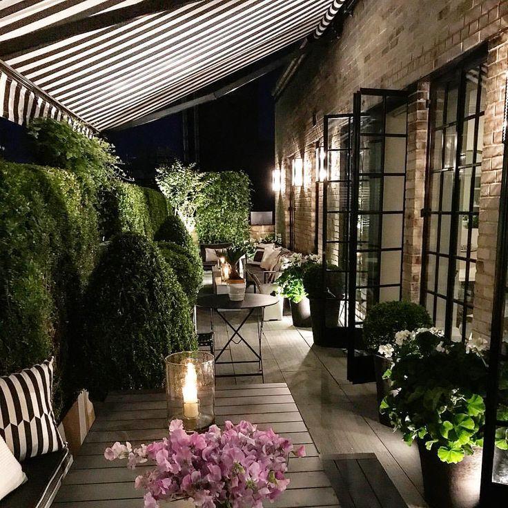Preciosa varanda o terraza, dependiendo del momento, lol, gracias a su espectacular toldo!, linda combinacion de muebles y accesorios ad doc con el tema.  Arbustos, decoracion floral, maceteros se muy buen gusto, al igual el  muro verde a lo largo del perimetro de este gran habitat, tanto como de noche y de dia... <v>
