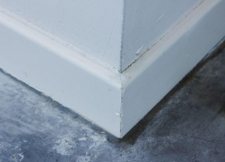 De hoek van 2 plinten die samenkomen aan een hoek van een muur