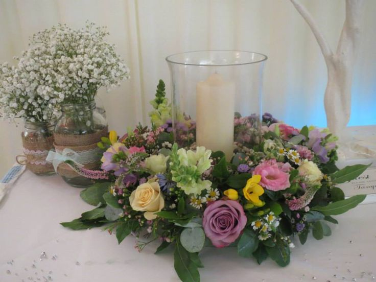 Hurricane vase wedding centrepiece with a floral surround