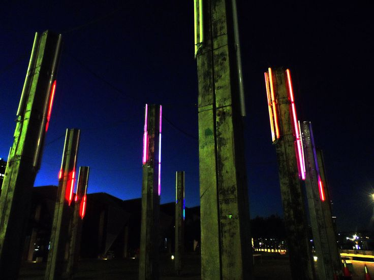 Interrupt Collective  2013    Trees are pou,  Those posts are pou  People are pou.  You are a pou[1]    Tūrama Pou is a site-specific work that inhales and exhales a flow of light through the Timber Forest on the Wellington Waterfront. Luminaire adorn the vertical timbers, visually responding to the tidal rhythms of the harbour.  Photographed at Wellington LUX: www.lux.org.nz