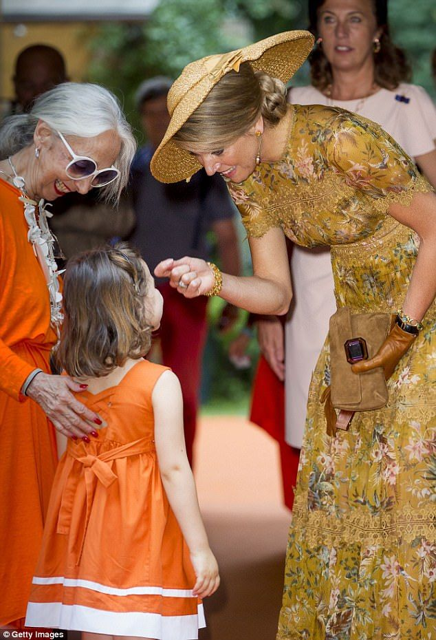 The Dutch Queen met with the Italian designer who had bought along her granddaughter who wore the same shade of orange as her grandmother