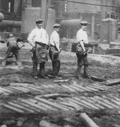 Iron workers standing near cooling iron pigs that were cast in sand molds.