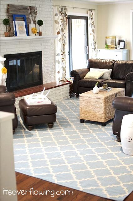Family Room With Blue Rug And Yellow Accents Brown Couches Rattan Coffee Table