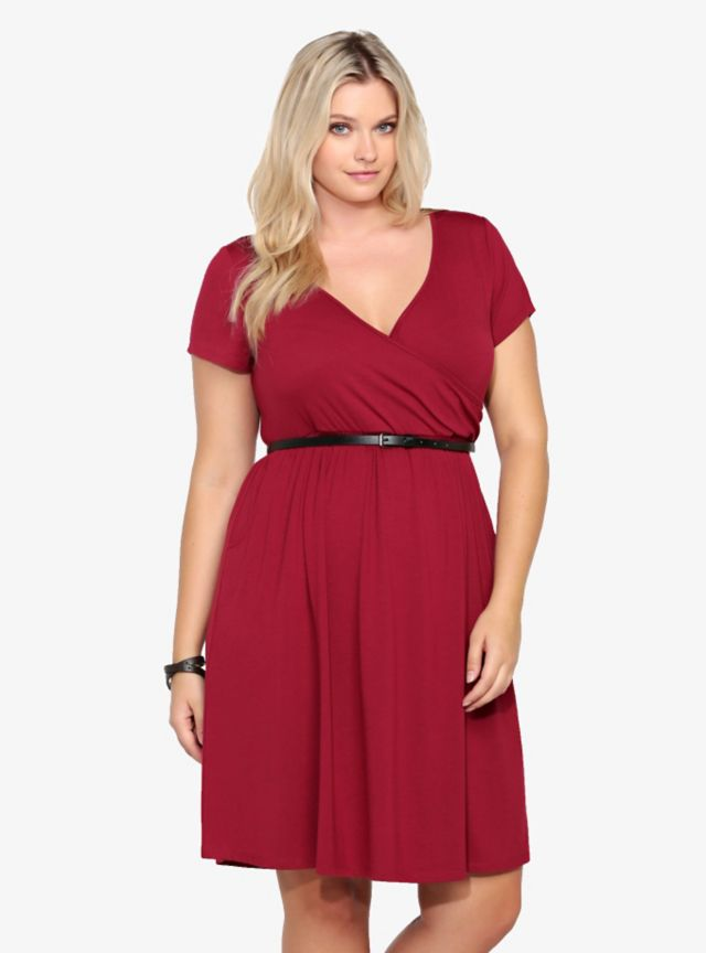 Super soft and lightweight, this burgundy red jersey knit dress is a perfect way to add a pop of color to your wardrobe. The figure-flattering silhouette has a faux-wrap surplice neckline, slight smocking around the waist, includes a black skinny belt and has skirt pockets that we absolutely love.