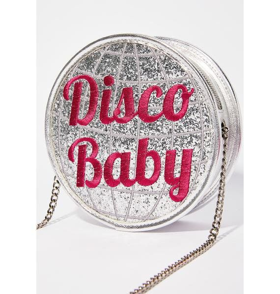 "Sugar Thrillz Disco Baby Bag will show 'em what you are. This cute af crossbody bag has a silver chain strap, a sparkly silver disco ball shape with pink ""Disco Baby"" text, and a top zipper closure."