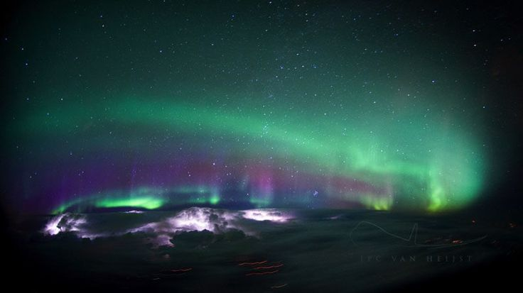 Glowing auroras above, glowing thunderstorms below.