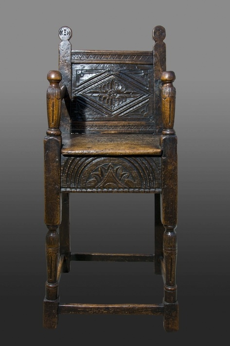 A late Elizabethan oak and fruitwood child's high chair. Carved fruitwood back panel with lozenge and leafy spandrels, seat rails carved with a single large lunette.