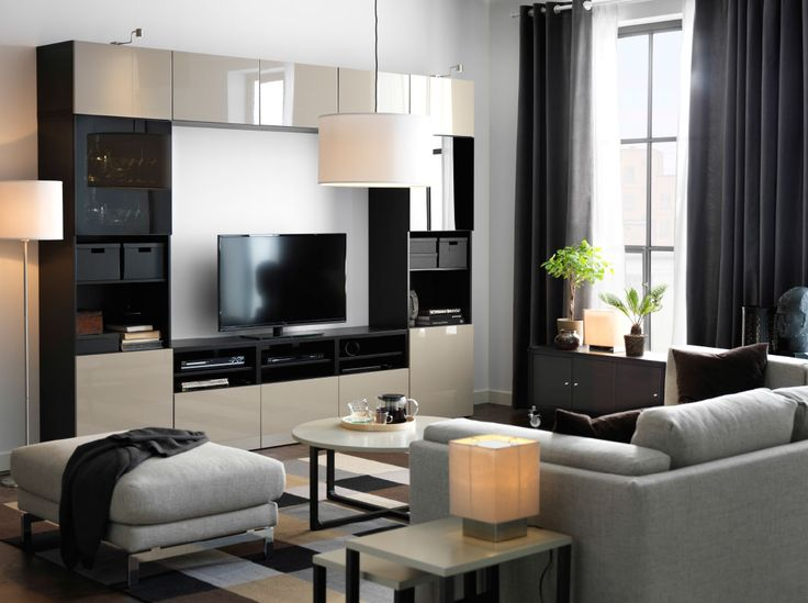 A large TV storage combination in black-brown with beige high-gloss doors and drawers. Combined with a sofa and footstool with light grey covers.