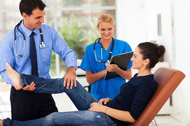 An orthopedist examining a patient.