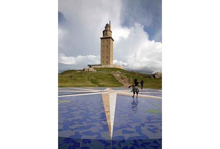 Torre de Hércules de La Coruña. La Torre de Hércules es el símbolo más característico de la entrada al puerto de La Coruña, en Galicia. Fue construida por los romanos en el siglo I, y desde entonces se ha mantenido en pie, aunque su configuración actual se debe en buena medida a la restauración llevada a cabo en el siglo XVIII. Su nombre original era Farum Brigantium. Tiene 55 metros de alto y está edificada sobre una roca que de 57 metros de altura.  XURXO LOBATO