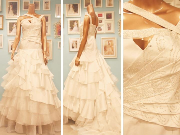 Asymmetrical wedding gown by Camille Garcia made of duchess satin featuring a beaded bodice and tiered skirt.