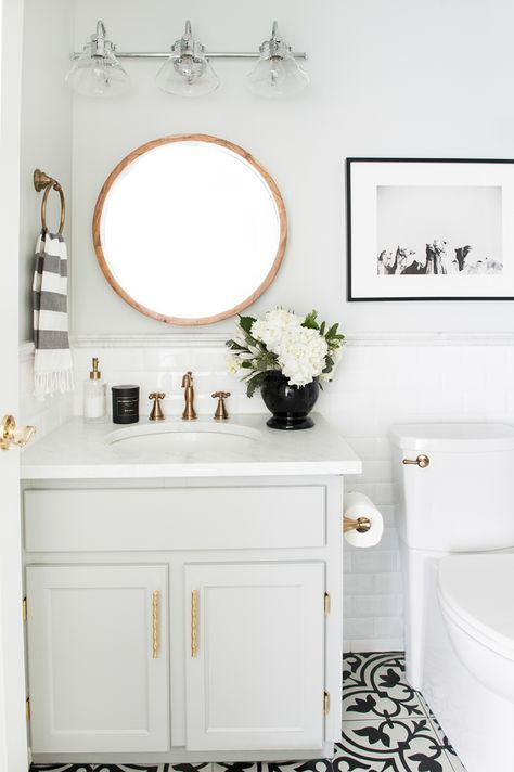 A small bathroom with huge character! An all white bathroom with gold fixtures feels luxurious.