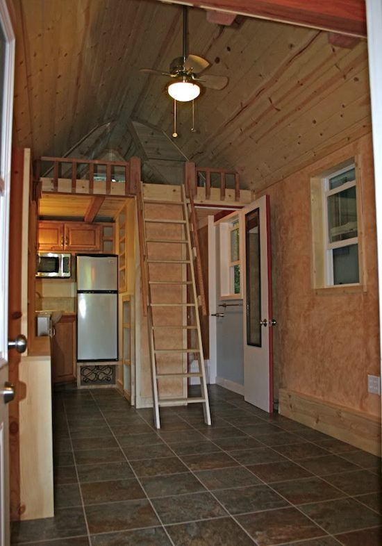 tiny house with two sleeping lofts on either end and a porch entrance one of the best tiny house kitchens ive seen and a very comfortable bath
