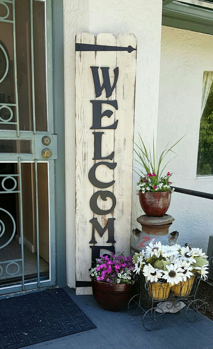 Welcome sign. Cedar boards, sanded, paint, sand to distress, then stain. Add painted wooden letters of choice and iron brackets for detail.