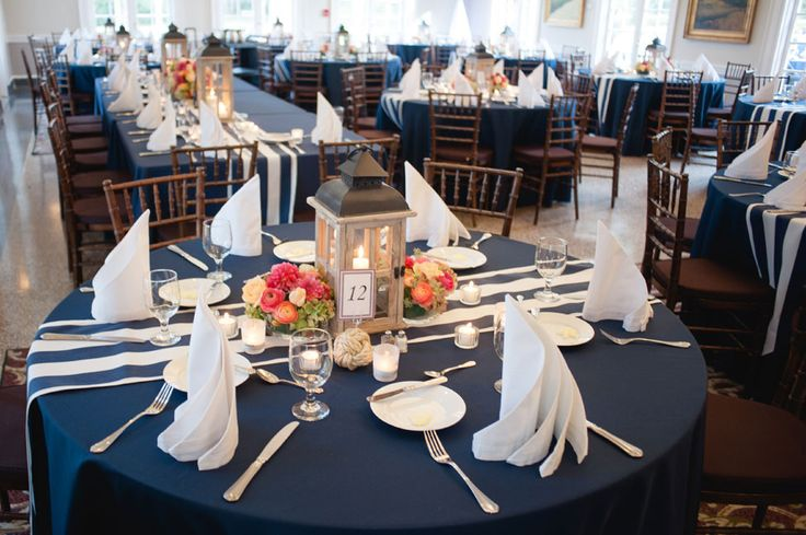 Navy tables, navy striped runner, sail fold napkins, wood lanterns & bright coral hues flowers | Coral & Navy Vintage Inspired Nautical Wedding At The Ribault Club Jacksonville Florida | Photograph by Britney Kay Photography   http://storyboardwedding.com/vintage-nautical-wedding-ribault-club-jacksonville-florida