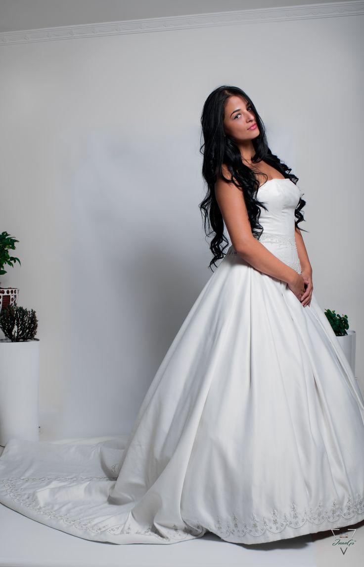 Vestido de novia strapless, falda con prenses anchos y cola, con bordados.