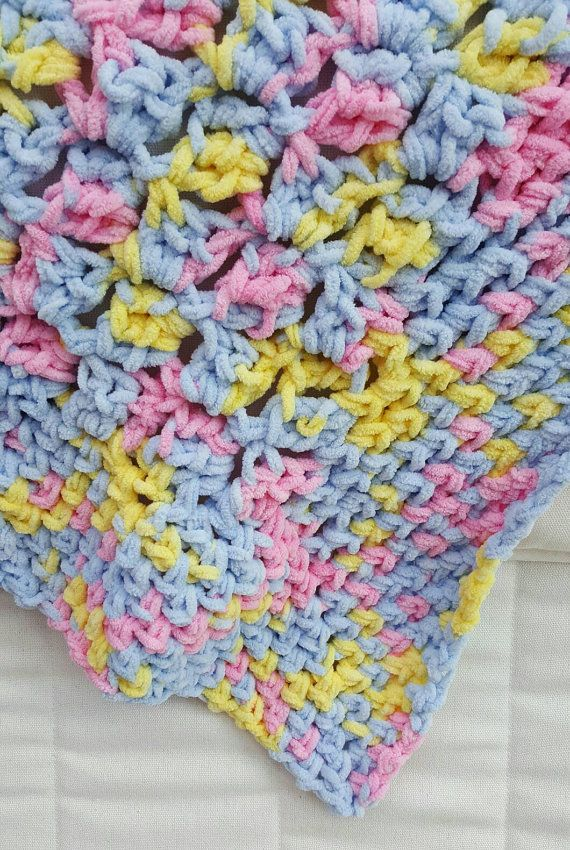 A beautiful, snugly, hand crocheted baby blanket made in baby blue, baby pink and pale yellow. Made from a cosy fleece bulky yarn, this blanket is thick and warm. Perfect for baby in the winter months.  Measuring ~87cm (36 inches) square this blanket is perfect size to keep baby or toddler cosy in pram, car seat, cot or Moses basket.  The soft fleecy yarn is 100% polyester making it machine washable and easy to care for.  A perfect new baby gift or a baby shower present. This blanket is one…