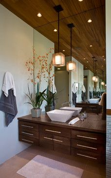 Wood warms up the look and feel of this bathroom. Mirrors help reflect lots of light around the room.