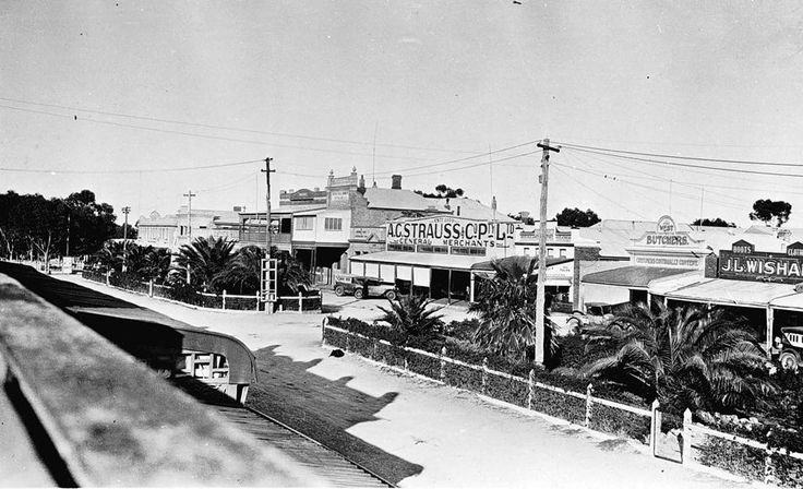 Main street Rainbow 1930. Shops on the other side of the street include JL Wishart jeweler; AG Strauss general store & West's butcher shop. Wishart store incorporated two shops, the jewelers [at right below the sign] & a drapery [at left below the sign]. A sausage factory was at the rear of West's next to which is a laneway. On the other side of the lane is Congoleon's cafe. The 2 storey building with the veranda is the Middle pub & the National Bank is between that & AC Strauss