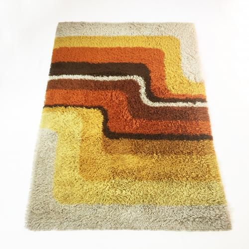 This rug is an example of 1970s pop art interior. It is made with a rya weaving technique and was designed in the 1970s and manufactured by Desso in the Netherlands. It is made from polyacryl wool and is still in a very good vintage condition. The rug features bright colors such as red, yellow, orange and brown. The original producer tag is still underneath the rug.