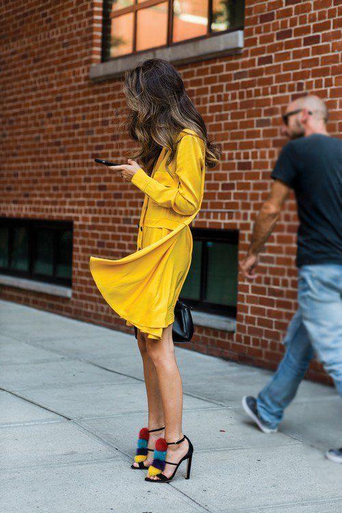 f6eee12918 Chica usando un vestido amarillo y zapatos elegantes en color negro con  aplicaciones de pompones en color azul rojo y amarillo