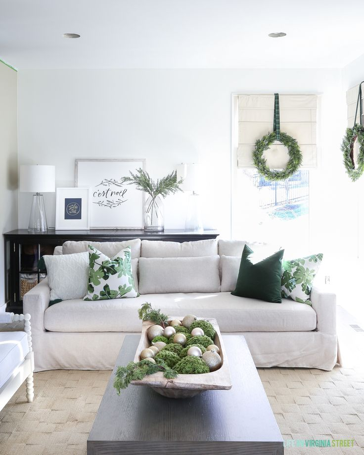 Christmas living with a linen York Slope Arm Sofa from Pottery Barn. I love the dark green velvet and fig leaf pillows and the wreaths on the windows! Large dough bowl filled with ornaments and greenery. The artwork is from Lindsay Letters. So perfect for the holidays! #christmaslivingroom #christmasdecor #livingroom #whitedecor