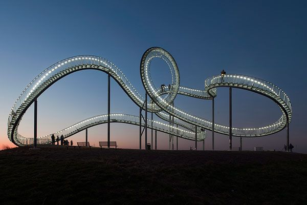 Magic Mountain is a large scale roller coaster sculpture near Duisburg, Germany. As visitors approach the sculpture they are surprised to learn that it is not a typical roller coaster, rather a long flight of variable steep steps. Led-lights are integrated into the handrails, highlighting the flight of stairs so the sculpture is accessible at night as well day. The design is by Heike Mutter and Ulrich Genth.