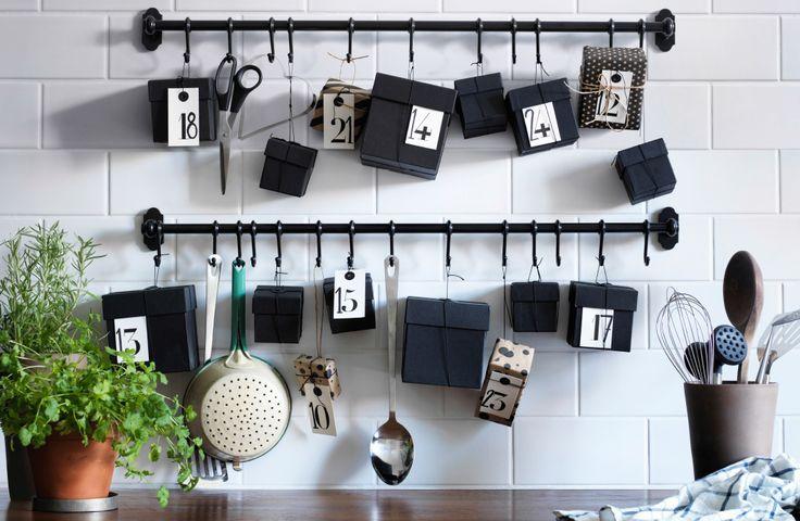 Kuchyňa s bielym obkladom a čiernou závesnou tyčou. Náčinie, ktoré obyčajne na tyči visí, je odložené v nádobe a miesto neho na tyči visia vianočné darčeky.
