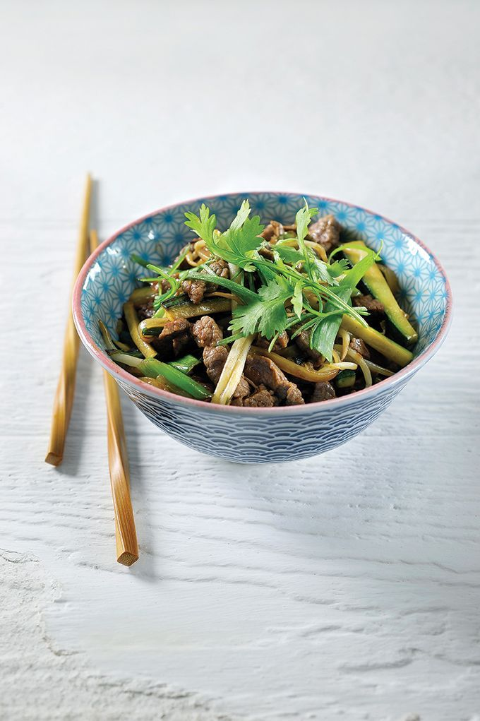 Bereiden: Snijd het vlees in heel fijne reepjes. Pel de ui en snijd in fijne halve ringen. Plet de gepelde teentjes look en snijd in grove stukken. Kook de eiernoedels 1 minuut in kokend water. Giet af en laat uitdampen. Snijd ondertussen de courgette in fijne lucifers. Plet het witte deel van de lente-ui en snijd in grove stukken. Snijd het groen fijn en zet opzij voor de afwerking.