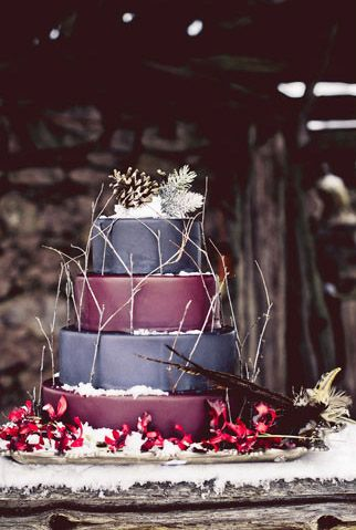 winter wedding cake in periwinkle blueish and plum with twigs and pine cones