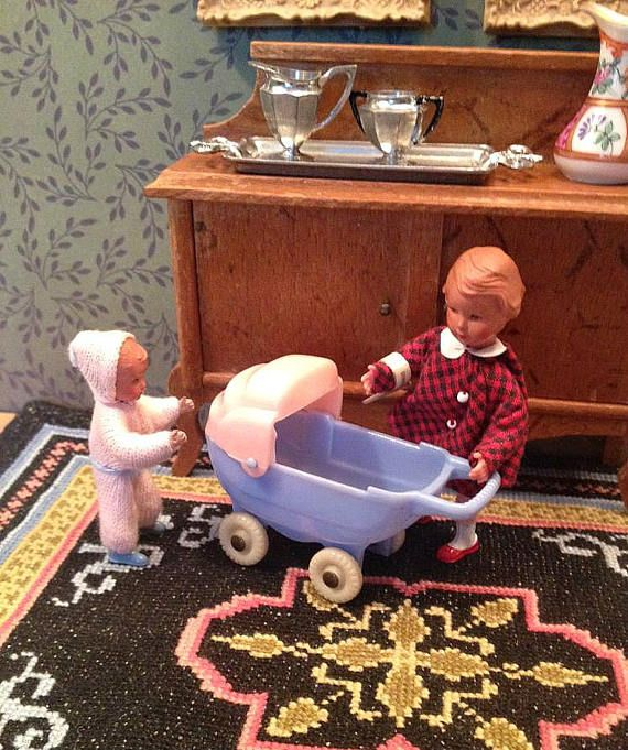Vintage miniature Acme baby buggy for the dollhouse from the 1940s. The little plastic doll buggy has a pink hood that swivels on the blue body of the buggy. The baby carriage is in very good condition with all four original tires and no cracks or breaks. The buggy is shown with