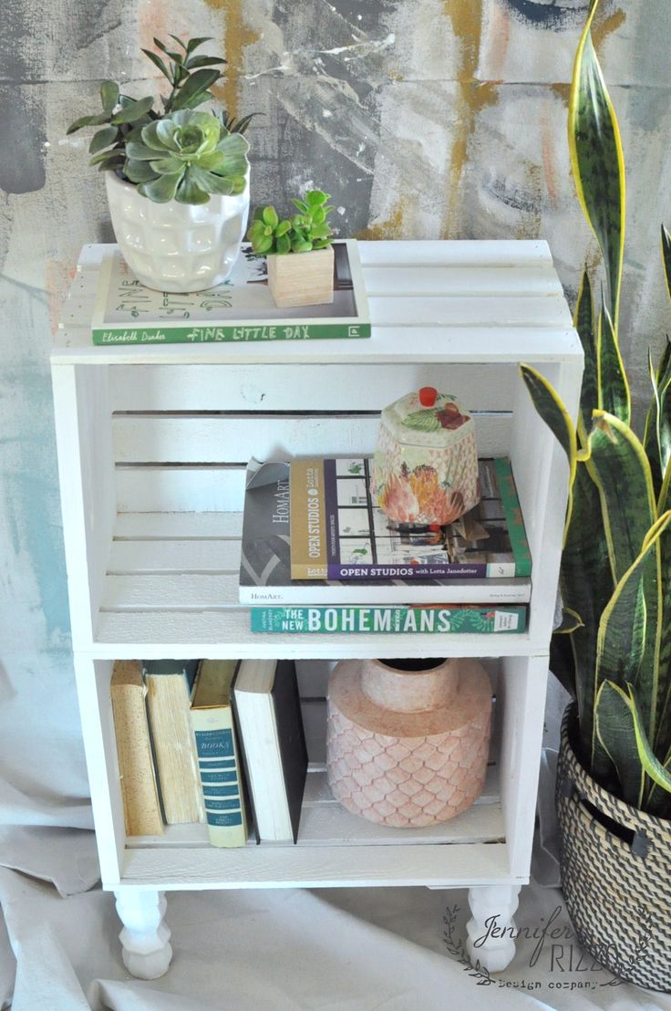 Make a DIY crate side table from craft store crates and some wood feet from  the home improvement store. This is a great way to make inexpensive storage.