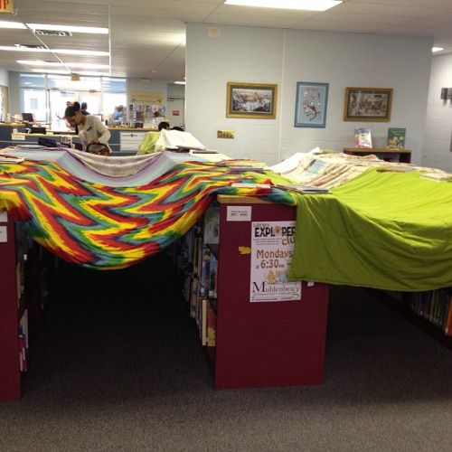 A fun bookshelf idea for librarians -- turn your the shelves in the children's book section into blanket forts!