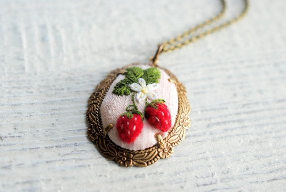 Hand embroidered strawberry pendant.