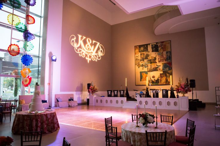 Wedding lighting design by BEYOND. Custom monogram projected on sculpture, atrium washed with LED uplighting changing colors throughout night, dance floor washed with light, tables spot lighted to highlight floral design. Planner Diamond Affairs photos by John Cain Sargent