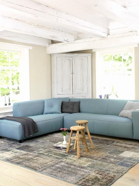 Een gave, grote loungebank als rustpunt van de dag, en een stoer patchwork kleed!
