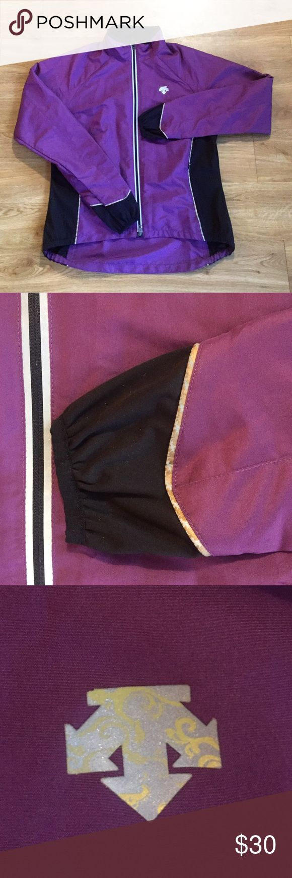 "Descente Windbreaker Fantastic purple and black windbreaker made by Descente. It has a patterned trim as shown in the picture of the sleeve. Front zip and a back zipper pocket. The top of the back has sit slits, with a breathable mesh inside. Length of front: 23"" Length of back: 26.5"". Pit-to-pit: 20"". Excellent pre-loved condition. No trades :) Descente Jackets & Coats"