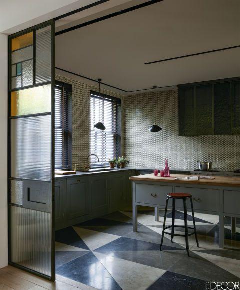 En unadosado victoriano en Inglaterra, los muebles de cocina, de Plain English, se pintaron con el color Pure Grey 6 de Papers andPaints. Las lámparas de techo son de Serge Mouille, de alrededor de 1955. En la pared, azulejos de Neisha Crosland. El suelo está formado por tres tipos de piedra caliza.